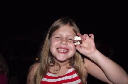 UUMAN members' child eating a s'more at camping trip.